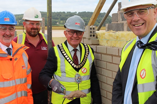Cllr Andrew Moulding, EDDC Chairman (centre), performs the topping out ceremony at Blackdown House, by cementing in the final brick, l-r are Cllr Ian Thomas Leader of EDDC, Adam Phillips of MAP Building Services (local firm of contractors used by Interserve) to the right of Cllr Moulding is Paul Gale, Divisional Director South West Interserve (EDDC's contractors for Blackdown House)