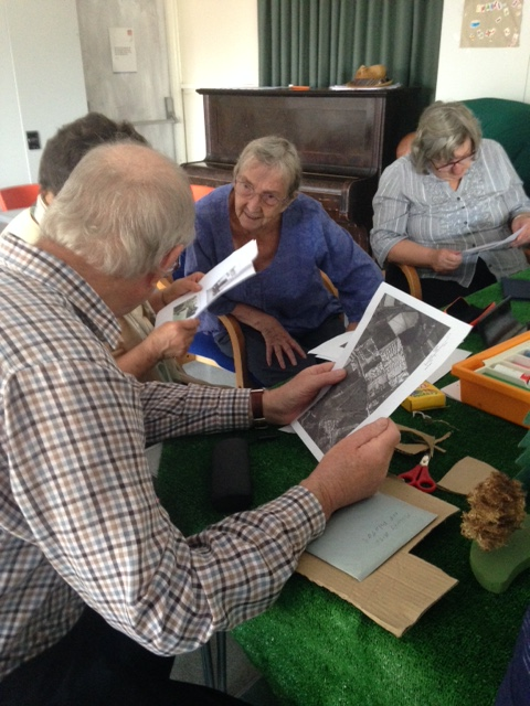 East Devon District Council tenants discussing old photographs of the Millwey Camp where they spent their childhoods