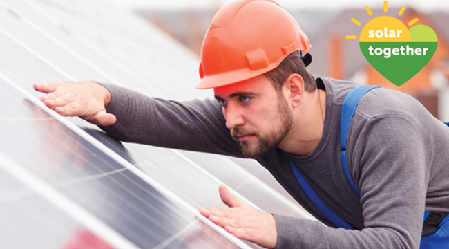 Worker fitting solar panels on a roof